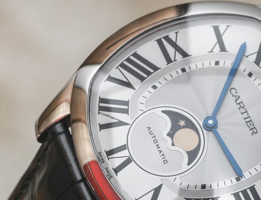 The silver-plated dials fake Drive De Cartier WGNM0008 watches have black Roman numerals, blue hands and moon phases at 6 o'clock.
